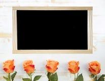 Orange rosor och tömmer den svarta svart tavlan Fotografering för Bildbyråer