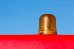 Orange rotating warning light. Orange flashing light installed on the roof of the red vehicle Stock Photography