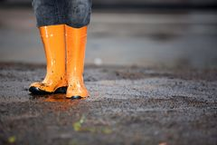 Orange rubber boots in a dirty puddle Stock Photos