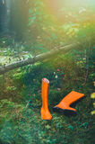 Orange rubber boots in the forest. Orange rubber boots in a Sunny forest lying on the green grass Stock Photos