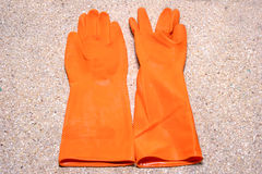 Orange rubber gloves on the floor Stock Photography