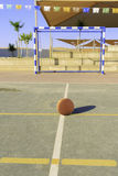 Orange rubber soccer ball front of gates. On the court Royalty Free Stock Images