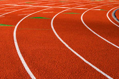 Orange rubberized Track & field track. Detail of the turn of a orange rubberized Track & field track  Tracks Stock Image