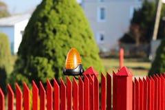 Orange rumlarmljus som lokaliseras på en hyreshus för tegelstenstaketstolpehögtalaranläggning på ingången till ett privat skyddat royaltyfri fotografi