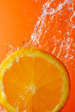 Orange and running water. Orange slice under flowing water - concept of refreshment Royalty Free Stock Images