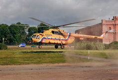 Orange russian Mi-8 helicopter is landing on grass lawn. Stock Photography