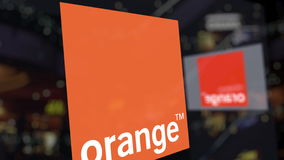 Orange S.A. logo on the glass against blurred business center. Editorial 3D rendering Stock Image