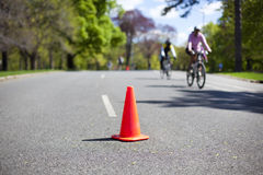 Orange safety cone on the road. With bicycle riders passing by Royalty Free Stock Photography