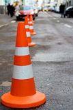 Orange safety cones. A row of orange safety cones warns of danger ahead Royalty Free Stock Photos