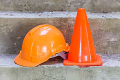 Orange safety helmet and cone Stock Image
