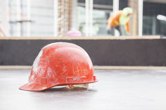 Orange safety helmet in construction with worker background. Orange safety helmet in construction with worker background Stock Photo