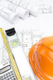 Orange safety helmet and rolled. Safety helmet and tape measurement tools over architectural blueprint Stock Photos