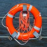 Orange safety ring and rope. Orange safety ring lifebuoy hanging on holder royalty free stock photo