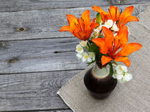 Orange saffron lilies and jasmine  flowers on wooden table Stock Image
