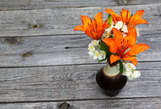 Orange saffron lilies and jasmine  flowers on wooden table Royalty Free Stock Image
