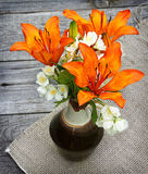 Orange saffron lilies and jasmine  flowers on wooden table Stock Photography