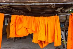 Orange and saffron robes of Buddhist monks hanging on wooden.Tha Stock Images