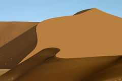 Orange sand dune with wave like shadow Royalty Free Stock Photos