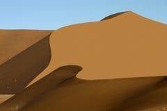 Orange sand dune with wave like shadow Royalty Free Stock Photos
