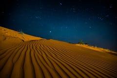 Orange sand dunes at night Stock Images