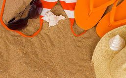 Orange sandals  and sunbathing accessories at sand Stock Images