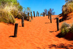 Orange sandy path going uphill in Australian outback Royalty Free Stock Images