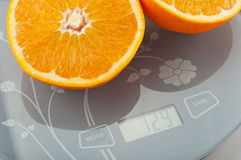 Orange on the scale. Weigh the orange on the scale Royalty Free Stock Images