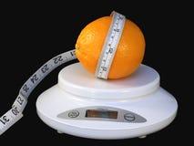 Orange on scale. Juicy navel orange with tape measure on white scale isolated on black background Stock Photography
