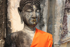 An orange scarf was put on the shoulder of a statue of Buddha (Thailand) Royalty Free Stock Images