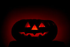 Orange scarry pumpkin with burning eyes on dark stock image