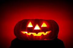 Orange scarry pumpkin with burning eyes on red Royalty Free Stock Photography