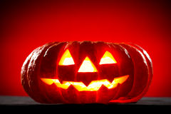 Orange scarry pumpkin with burning eyes on red Royalty Free Stock Photo