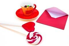 Orange Schale mit bunten Knopf-förmigen Schokoladen, rotem Umschlag und Lutschern Lizenzfreies Stockfoto