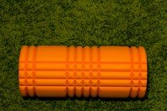 Orange Schaumrolle auf grünem Hintergrund Stockfoto
