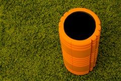 Orange Schaumrolle auf grünem Hintergrund Stockbild