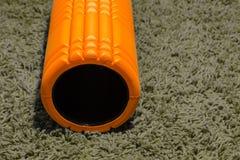 Orange Schaumrolle auf grauem Hintergrund Stockbild