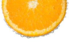 Orange Scheibe im klaren sprudelnden Wasser-Blasen-Hintergrund Lizenzfreie Stockfotos