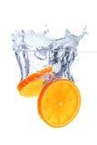Orange Scheiben, die in das Wasser fallen Stockfoto