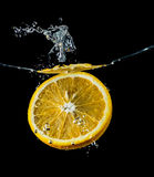 Orange Scheiben, die in die Wassernahaufnahme, Makro, Spritzenwasser, Blasen, schwarzer Hintergrund fallen Lizenzfreie Stockfotografie