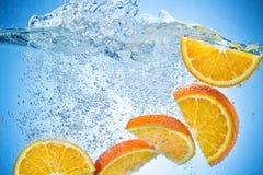 Orange Scheiben, die unter Wasser mit Spritzen fallen Lizenzfreie Stockbilder
