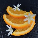 Orange Scheiben mit Wassertropfen und Blumen auf einem schwarzen Hintergrund Stockfotos
