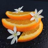Orange Scheiben mit Wassertropfen und Blumen auf einem schwarzen Hintergrund Stockbild