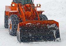 Orange Schneepflug löscht die Straßen Stockfoto