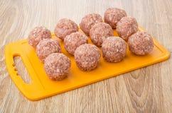 Orange Schneidebrett mit rohen Fleischklöschen auf Tabelle Lizenzfreie Stockfotos