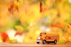 Orange School Bus Surounded By Falling Leaves Royalty Free Stock Photo