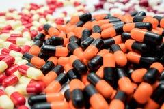 Orange, schwarz, weiß, rot, hellgelb, Kapselpillen Stockfotografie