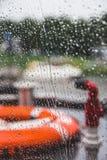 Orange Schwimmweste auf einem Boot während eines Regensturms, flacher dep Lizenzfreie Stockfotos