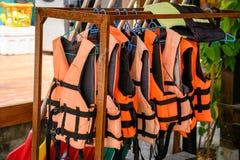 Orange Schwimmwesten, die am Gestell hängen stockfoto