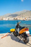 Orange scooter standing on wharf of Greek harbour. With city budings in background, Greece Royalty Free Stock Photography