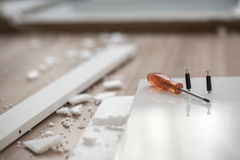 Orange screwdriver lying on a wooden element of a new furniture Royalty Free Stock Photo